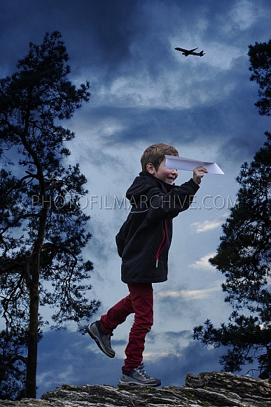 Boy playing with paper airplane.