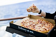 Norwegian Epic. Woman eats pizza from room service at stateroom balcony.